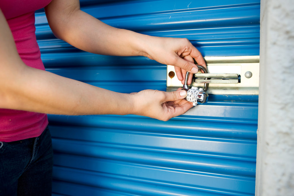 close up of woman's arms and hands locking a storage unit